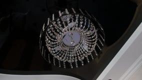 Close-up van mooie kristalkroonluchter om vorm het hangen van het plafond in het binnenland stock footage