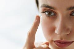 Close-up van Mooie Vrouw die Ooglens in Oog toepassen stock afbeelding