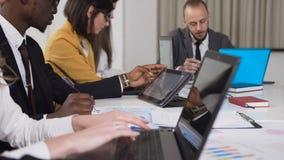 Close-up van multi-etnische groep jonge bedrijfsmensen die bij de lijst aangaande conferentie zitten en aan computer werken stock video
