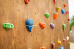 Close-up van multicolored haken voor rotsklimmer op houten muur in openluchtspeelplaats Kleurrijke abstracte achtergrond royalty-vrije stock fotografie