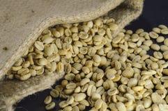 Close-up van niet geroosterde koffiebonen in hennepzak op zwarte achtergrond Royalty-vrije Stock Foto's
