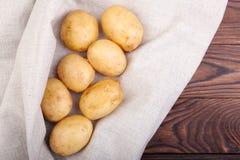 Close-up van nieuwe aardappels op een wit servet, voedzame groenten voor gezonde de zomerschotels op een donkere bruine achtergro Stock Afbeelding