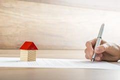 Close-up van nieuwe huiseigenaar die een contract van huisverkoop of mor ondertekenen stock foto's