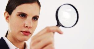Close-up van onderneemster die door vergrootglas kijken stock videobeelden