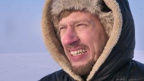 Close-up van ontdekkingsreiziger op middelbare leeftijd in kap en laag het letten op rightwards koud voelen en frustratie wordt g stock video