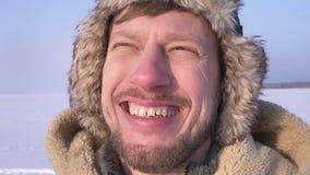 Close-up van ontdekkingsreiziger op middelbare leeftijd in kap en laag het letten smilingly op bij de zon en in camera op sneeuww stock footage