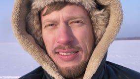 Close-up van ontdekkingsreiziger zetten het op middelbare leeftijd bij kap het letten calmly op in camera op sneeuwwoestijn die w stock videobeelden