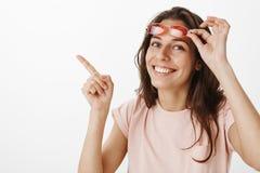 Close-up van opgetogen koele en modieuze jonge vriendschappelijk-kijkt wordt geschoten vrouwelijk opstijgend rode zonnebril die z stock foto's
