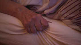 Close-up van oude woman'shand die in bed liggen