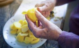 Close-up van oudere vrouwenhanden die aardappels snijden royalty-vrije stock afbeelding
