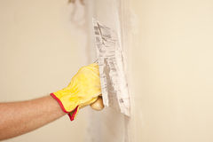De muurvernieuwing van het huis met schraper en cement Royalty-vrije Stock Afbeeldingen