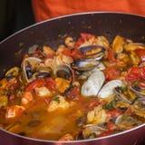 Close-up van pan met zeevruchtenschotel in tomatensaus wordt gekookt die Verse gestoofde Tweekleppige schelpdieren, Garnalen, mos Royalty-vrije Stock Afbeelding