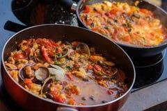Close-up van pannen met zeevruchtenschotel in tomatensaus wordt gekookt die Verse gestoofde Tweekleppige schelpdieren, Garnalen,  Stock Fotografie