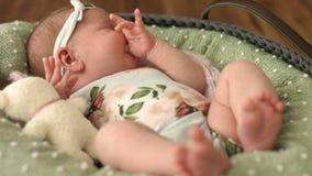 Close-up van pasgeboren meisje in mooie kleren met een bloemendruk en een hoofdband die in wieg ligt stock videobeelden