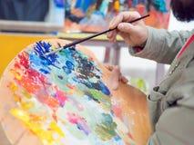 Close-up van penseel in mensenhanden die verven op palet mengen stock foto's