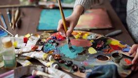 Close-up van penseel in vrouwenhanden die verven op palet mengen stock video