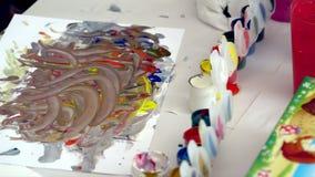 Close-up van penseel in vrouwenhanden die verven op palet mengen Heldere kleuren van verven stock videobeelden