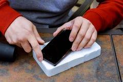 Close-up van Person& x27; s Hand die het Beschadigde Scherm op Mobiele Telefoon bevestigen stock afbeeldingen