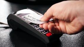 Close-up van persoon wordt die betaling zonder contact met creditcard voor het winkelen gebruiken geschoten die stock footage