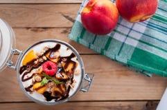 Close-up van perzikparfait met yoghurt, granola en chocoladebovenste laagje in een kruik, hoogste mening royalty-vrije stock afbeeldingen