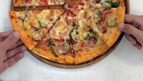 Close-up van pizza op een houten plaat Twee handen nemen stukken van pastei met worst, groenten, kaas, kruiden in het deeg royalty-vrije stock afbeeldingen