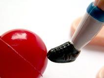 Close-up van plastic stuk speelgoed voetballervoet met rode bal Stock Foto's