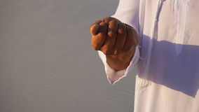 Close-up van portret en handen van jonge Arabische Sjeikkerel wordt geschoten in zandige woestijn op duidelijke de zomerdag die i stock footage