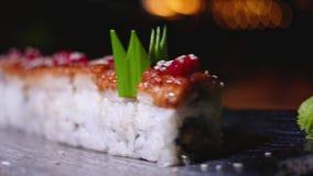 Close-up van prachtig verfraaide sushibroodjes op plaat met wasabi Kader Professioneel voorbereide en verfraaide sushi stock videobeelden