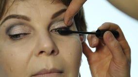 Close-up van professionele grimeurkleurstoffen de ogen van het model met een grote borstel de schoonheidsmiddelen van de manierin stock videobeelden