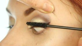 Close-up van professionele grimeurkleurstoffen de ogen van het model met een grote borstel de schoonheidsmiddelen van de manierin stock footage