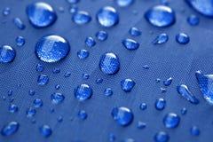Close-up van regendalingen op een blauwe paraplu Stock Afbeeldingen