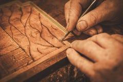 Close-up van restaurateurshanden die met antiek decorelement werken in zijn workshop stock foto