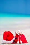 Close-up van rode Kerstmanzak en Santa Claus-hoed op strand De vakantie van de Kerstmisreis en de reis cuprise concept Strand stock fotografie