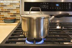 Close-up van roestvrij staal kokende pot op gasfornuis in eigentijdse huiskeuken voor de betere inkomstklasse stock foto's