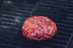 Close-up van rundvleeskotelet, voor hamburger, die in grill wordt gebraden, Stock Afbeeldingen