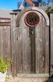 Close-up van rustieke houten poort met decoratief rond smeedijzervenster en een het planten troffel voor kloppers met twee verhaa stock afbeeldingen