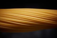 Close-up van ruwe spaghetti op een zwarte achtergrond Stock Afbeelding