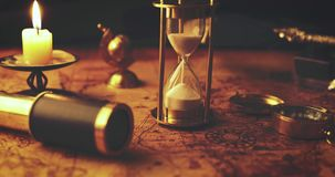 Close-up van sandglass die uit op oude wereldkaart lopen in kaarslicht stock videobeelden