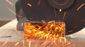 Close-up van schijf om metaal te snijden van de machtshulpmiddel die van de hoekmolen die een metaalprofiel snijden op de houten  stock videobeelden