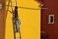 Close-up van schilder het schilderen muur van huis van geel in Burano Royalty-vrije Stock Fotografie