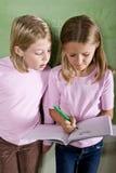 Close-up van schoolmeisjes die in klasse schrijven Stock Foto