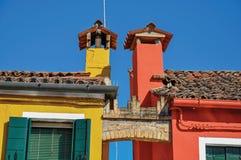 Close-up van schoorstenen en boog tussen kleurrijke terrasvormige huizen in Burano stock foto's
