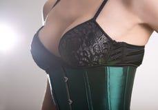 Close-up van sexy jonge vrouw in zwarte bustehouder en groen korset wordt geschoten dat Stock Foto