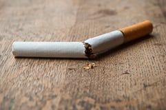 Close-up van sigaret op houten lijstachtergrond die wordt gebroken Royalty-vrije Stock Fotografie