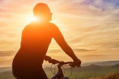 Close-up van silhouet die van fietser zich met fiets tegen mooie zonsondergang bevinden Royalty-vrije Stock Afbeelding