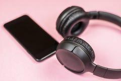 Close-up van slimme telefoon met hoofdtelefoons op een roze achtergrond stock foto's
