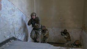 Close-up van speciaal krachtenteam die zich op de treden in een verlaten gebouw in een militaire opdracht bewegen stock footage