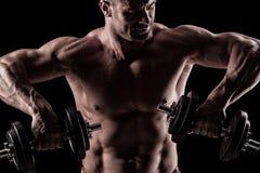 Close-up van spier jonge mens het opheffen gewichten op donkere backgrou royalty-vrije stock foto