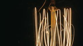 Close-up van spiraalvormige gloeilamp Langzaam verlicht Op een zwarte achtergrond stock video