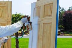Close-up van spuitpistool met verf schilderende Meester die houten deuren schilderen stock afbeelding